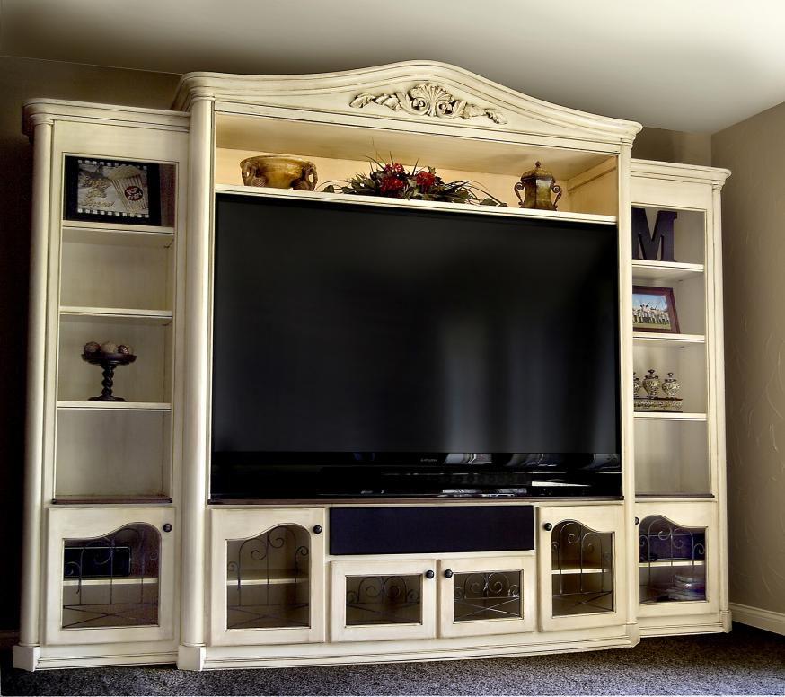 Tv entertainment center with custom designed handcarving and crown moulding with antique white finish.