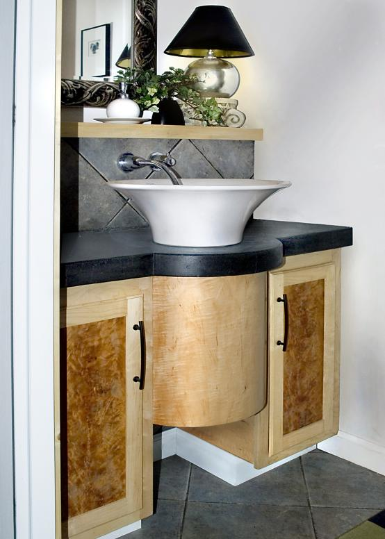 Maple bow front bathroom vanity designed to complement round vessel sink.