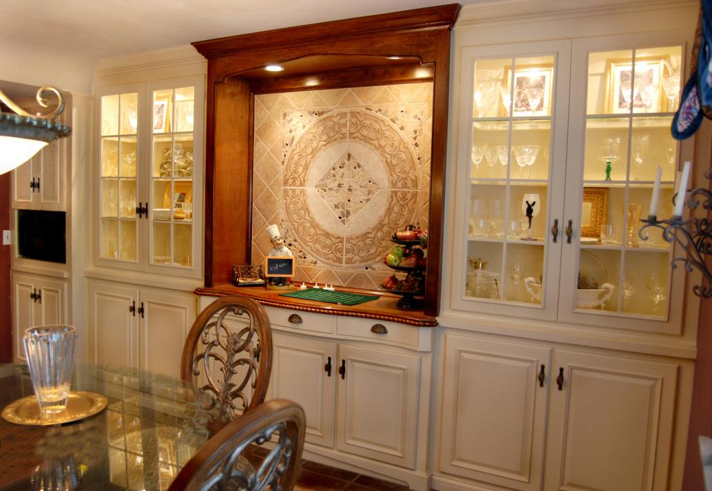 Lighted dining room buffet and cabinets with handcarved details.