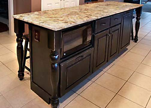 One of three pieces in matching set. Custom island base with space for microwave and trash with seating for five. Black distressed finish.