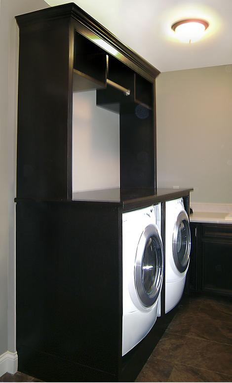 Laundry room washer/dryer enclosure with upper shelves and clothes hanging rod. Stained to match existing cabinets.