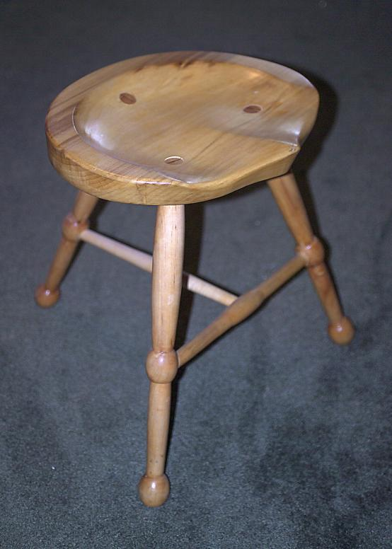 Three legged poplar and maple stool with hand carved scooped seat.